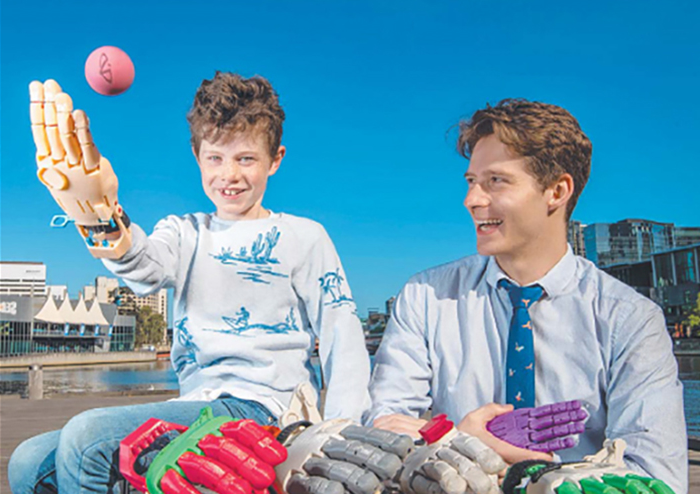 University of Melbourne engineering alum Matt Collinson with Mikko, 8, and his 3D-printed prosthetic hand