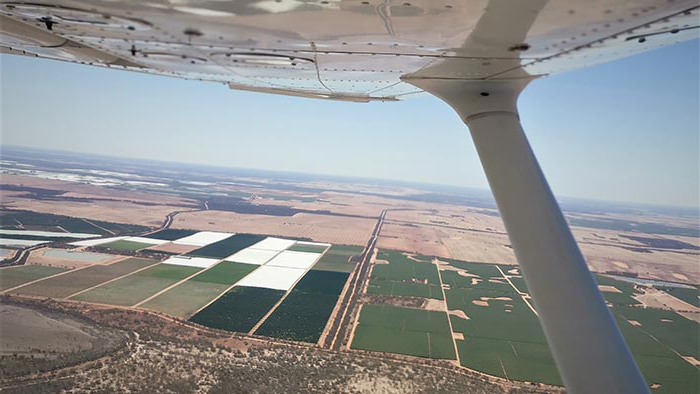 View of crops taken from air with wing of light aircraft visible