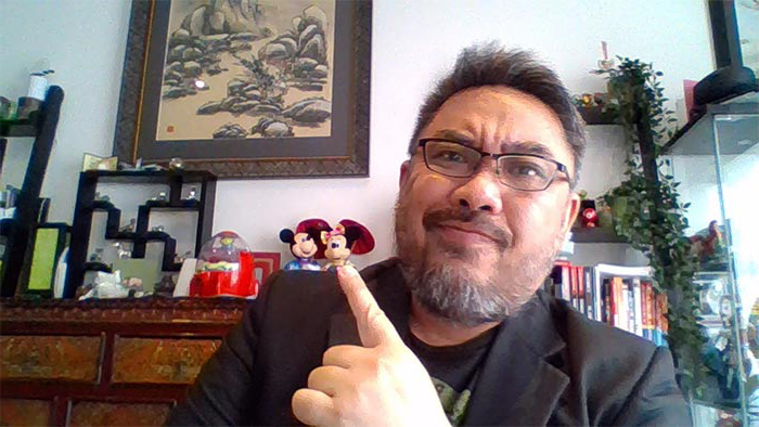 shanton昌 in home office with objects including Mickey 和 Minnie Mouse figurines behind him
